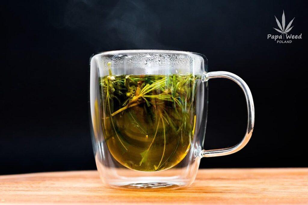 szklanka z zaparzoną herbatą z konopi, widać ziele, napój jest gorący, paruje